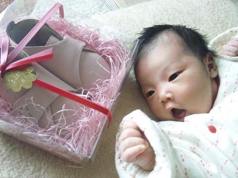 出産祝いのベビー靴と生まれたばかりの赤ちゃん