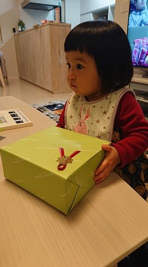 プレゼントの箱を持つ赤ちゃん