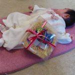 出産祝いのベビーシューズと一緒に写った赤ちゃん