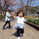 桜並木道を行進する赤ちゃん